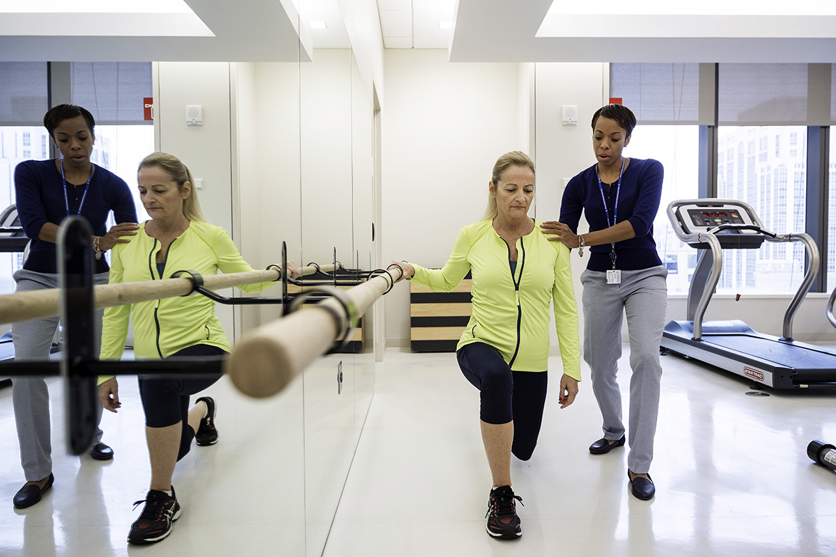 An MSK rehabilitation specialist helps a patient with physical therapy in the gym.