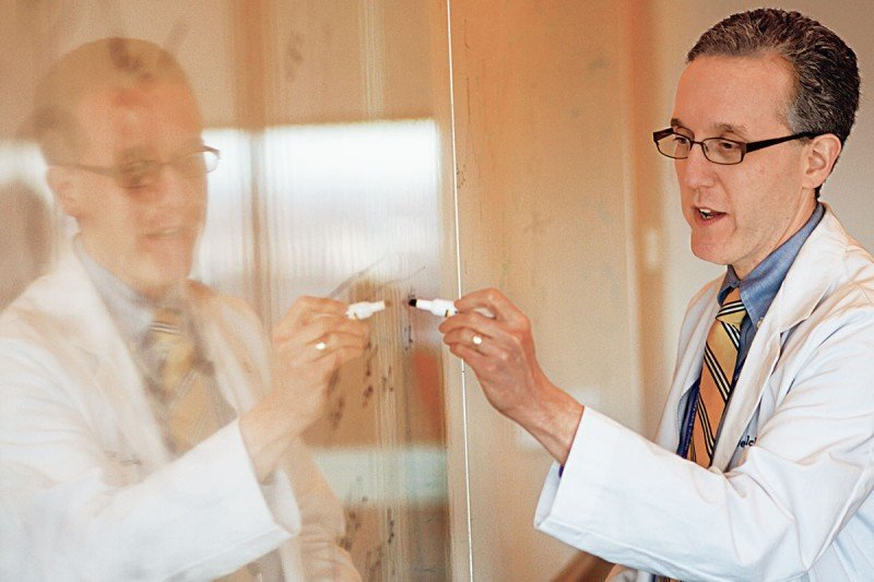 A doctor wearing a white lab coat writes on a white board with a marker.