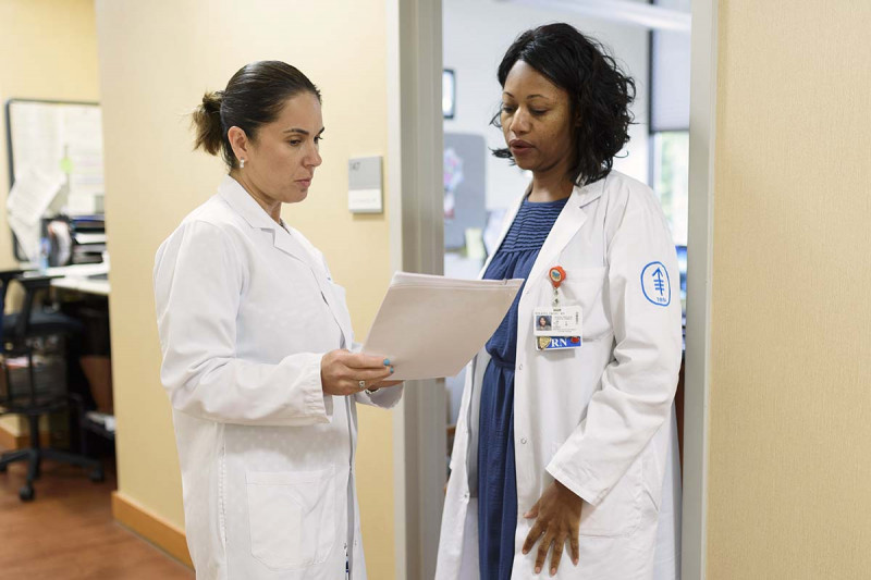 MSK Nassau medical oncologist, Zoe Goldberg, analyzes papers with fellow colleague.