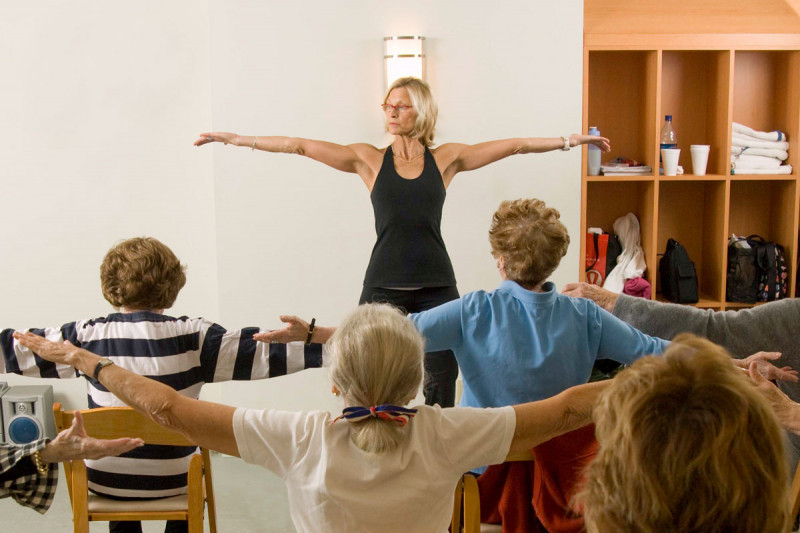 """Female instructor leading a """"chair yoga"""" class with female patients seated with back to camera and arms stretched to side."""