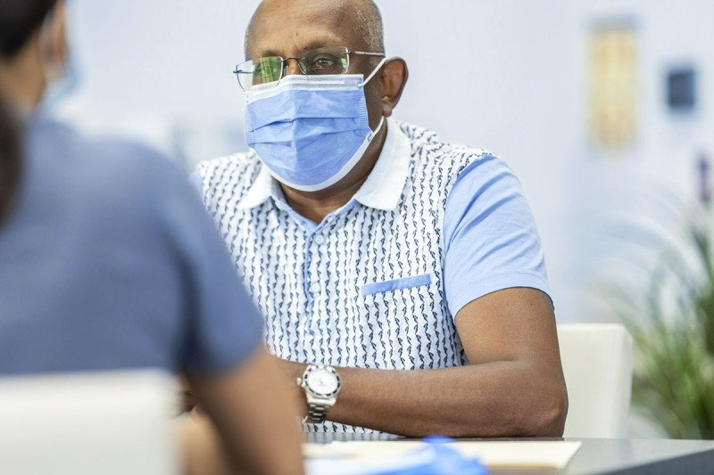 Black man conferring with female doctor in scrubs.