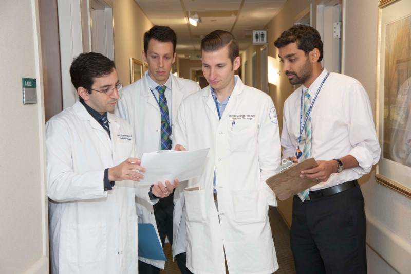 Radiation oncologist Sean McBride (center) reviews patient notes with resident Sam Bakhoum, Erik Anderson, and Suchit Patel.