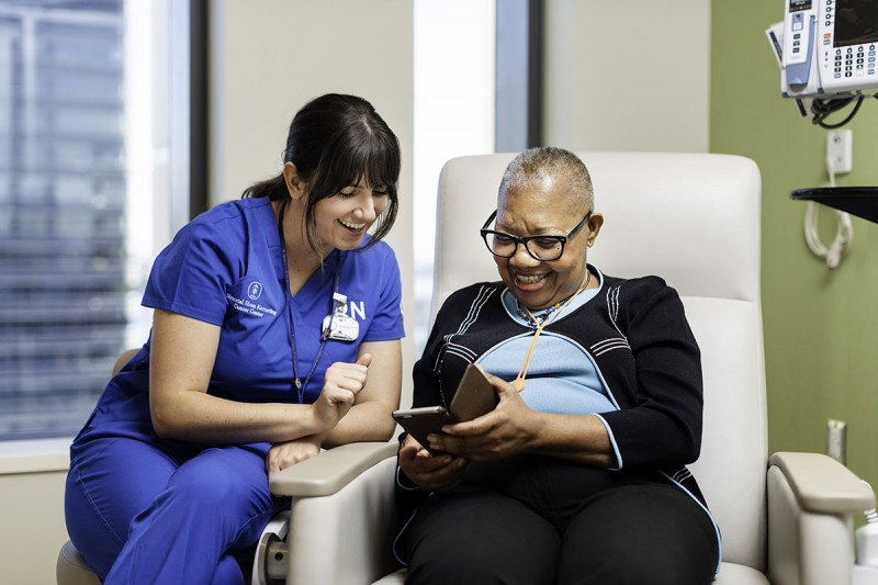 A female nurse talks with a female patient, who is sitting in an exam chair
