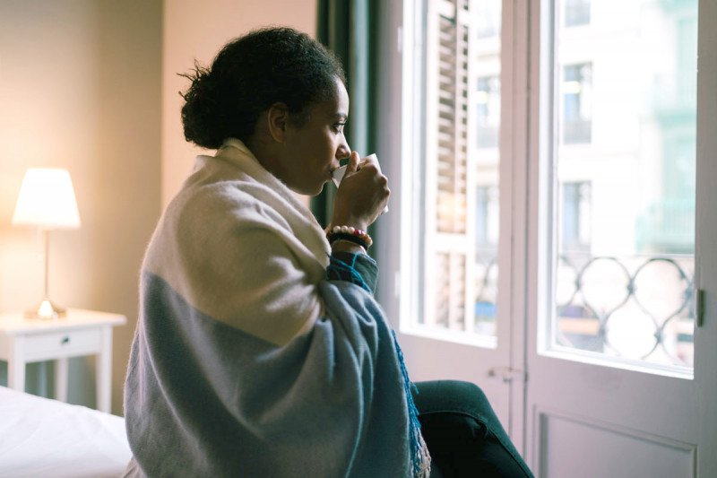 Woman looking out window while sipping from mug
