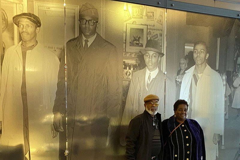 Dr. Smith's parents, Arthur and Barbara Smith, in front of a photograph of the Greensboro Four protest in 1960. Barbara's Smith cousin, Joseph McNeil (far right), is one of the members of the Greensboro Four