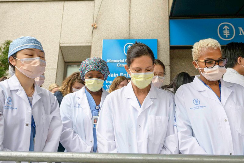 Four doctors wearing white coats and masks