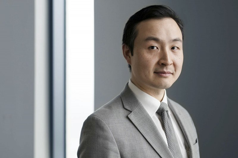 Medical oncologist Bob Li in front of a grey background