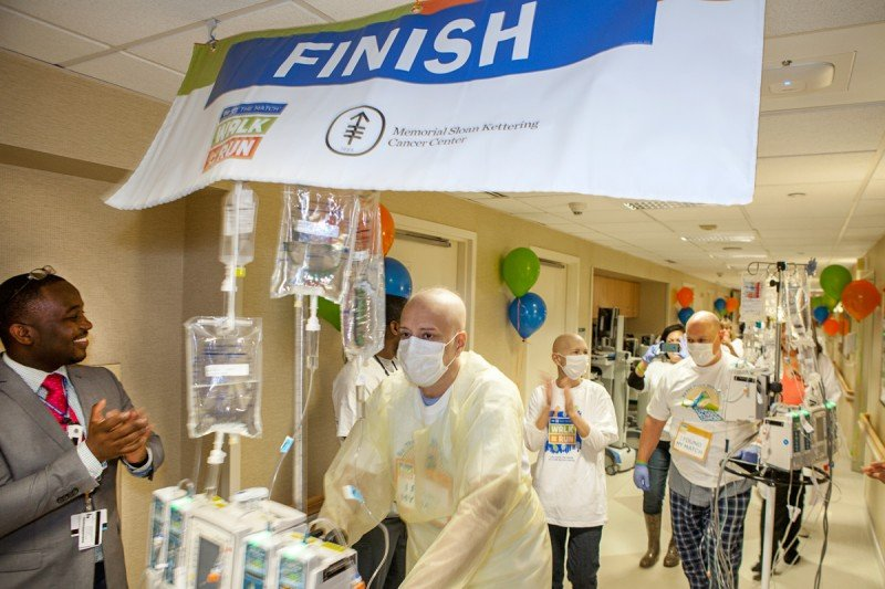 (From left) MSK patients Adam Lopranos, Eileen Grimes, and Jeffrey Scarpitti cross the finish line after walking the halls to support marrow transplantation.