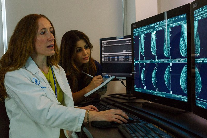 Memorial Sloan Kettering Cancer Center radiologist Sandra Brennan, MBBCh, BAO; FRCR, and interventional mammography technologist Elizabeth Mirabile looking at scans on a computer screen.