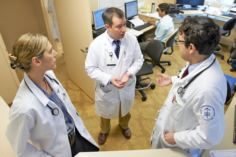 Medical oncologist Gregory Riely and two additional MSK physicians speak in a half circle.