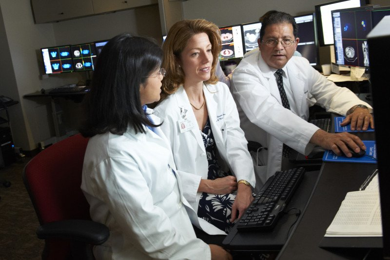MSK endocrinologist Mabel Ryder, surgeon Vivian Strong, and nuclear medicine doctor Jorge Carrasquillo sit together at a computer reviewing adrenal tumors.
