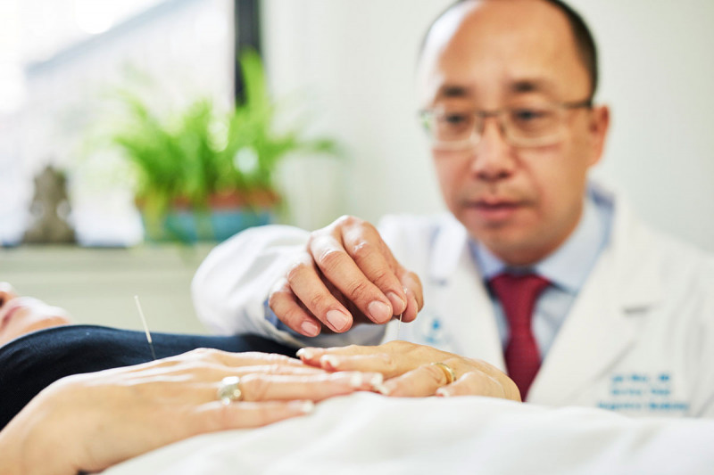 Male physician administering acupuncture to a patient