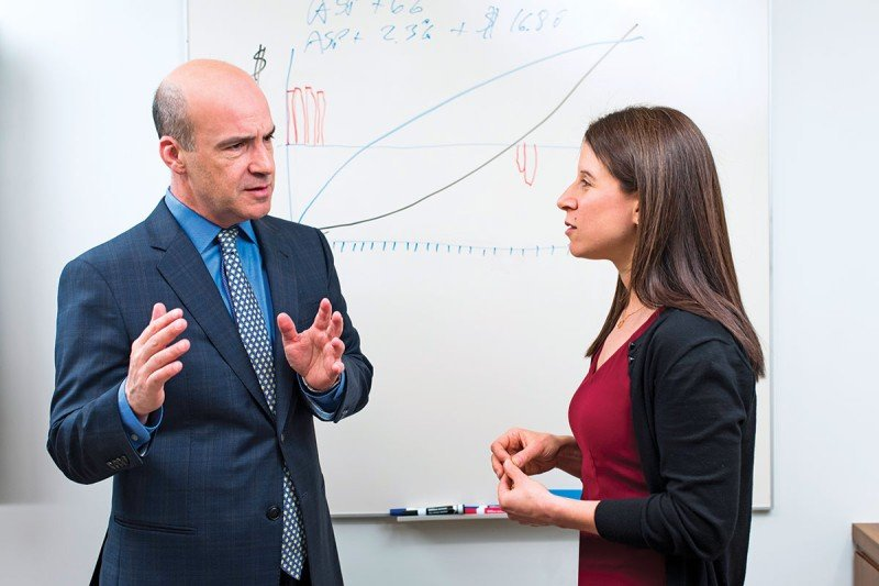 Man and woman talking in front of whiteboard