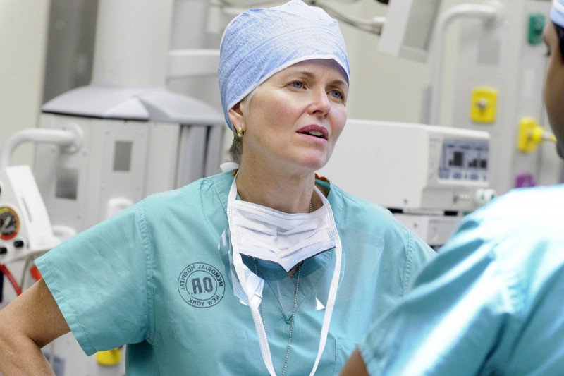 Surgical oncologist Mary Sue Brady speaks to colleague while in surgical scrubs.