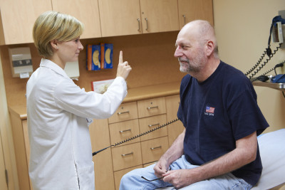 MSK nurse practitioner, Alison Gilgan, examines a male patient sitting in a chair.