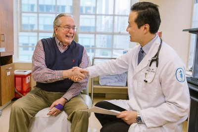 Albert Kuchler discussing his treatment results with MSK oncologist Bob Li at a recent clinic visit.