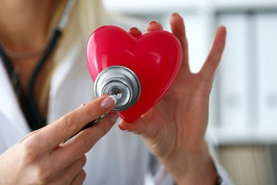 Female doctor holds stethoscope to red toy heart