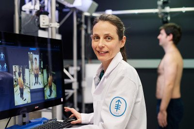MSK medical photographer, Daphne Demas, stands in front of a computer while screening a male patient for melanoma
