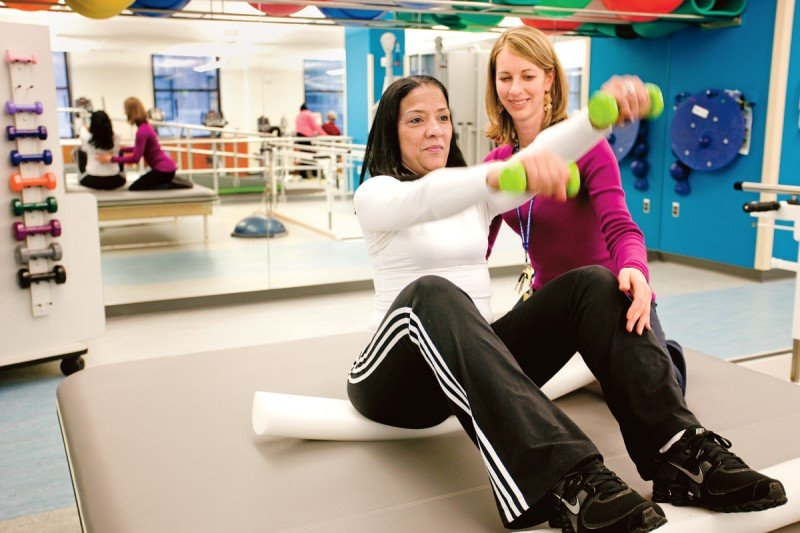 A patient does strength-training exercises as a physical therapist looks on.