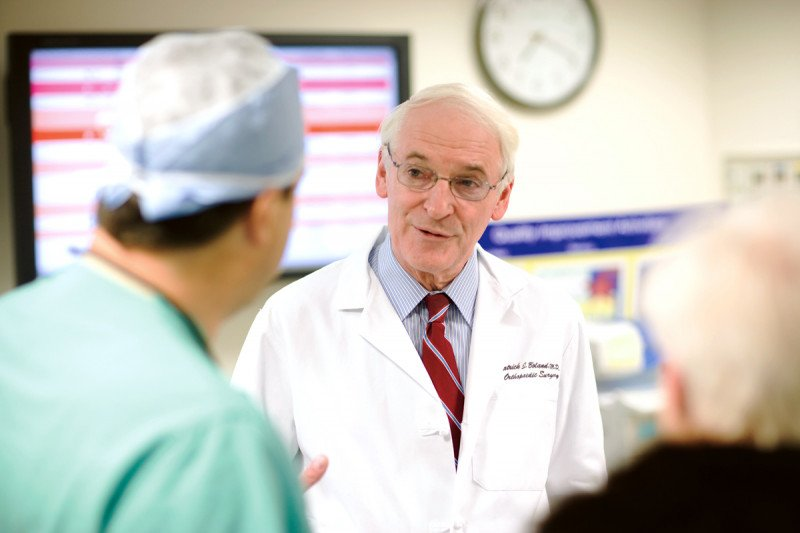MSK orthopedic surgeon, Patrick Boland, speaks with a male colleague who is dressed in scrubs.