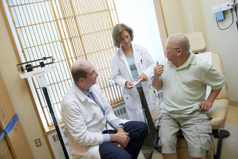 Two MSK doctors speak to patient with testicular cancer.