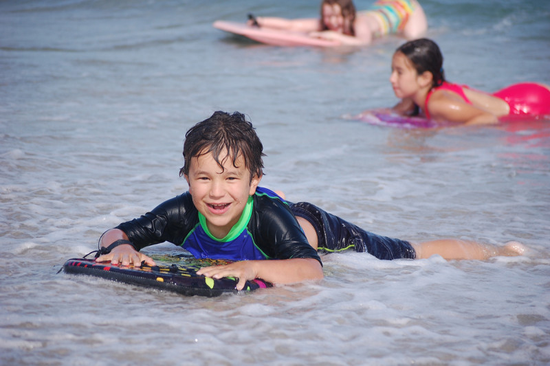 Smiling boy lying on board in the surf at the beach.