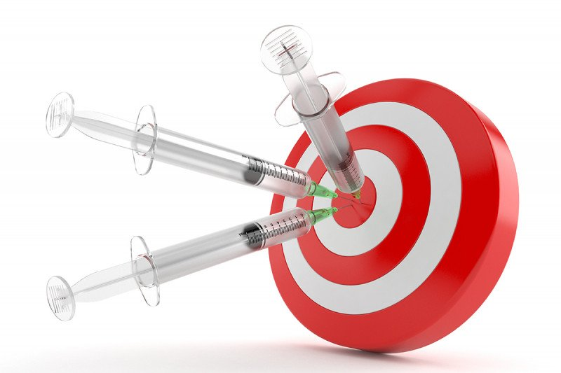 Three syringes stuck into an orange and white bull's-eye