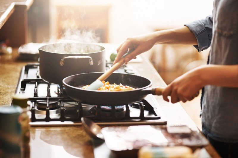 Person cooking food in a pan