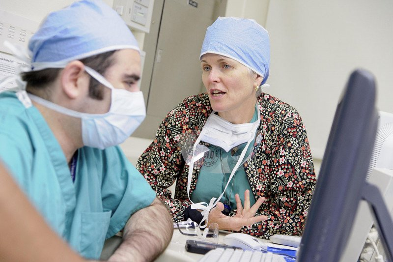 Melanoma surgeon, Mary Sue Brady, speaking with fellow MSK colleague in their masks and scrubs before a procedure