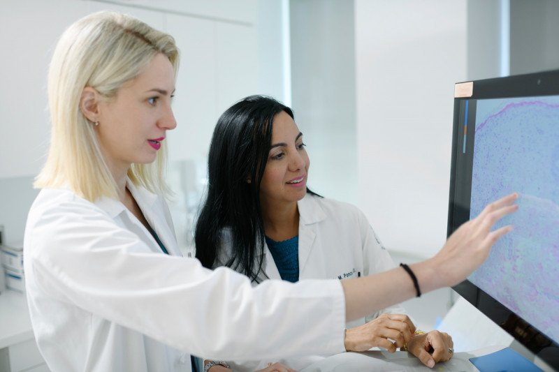 Dermatologist Alina Markova and hematologic oncologist Doris Ponce work at a computer showcasing GVHD cells together.
