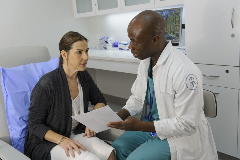 MSK Nurse Leader Corey Russell speaks with a patient concerned about nausea and vomiting following chemotherapy.
