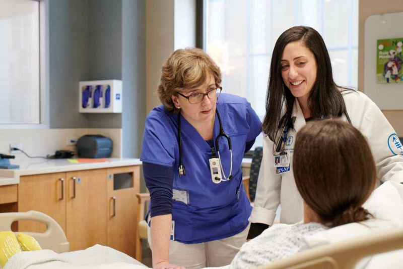 Nurse Mary Ann O'Grady and nurse practitioner Shanna Scalzo talk to a patient