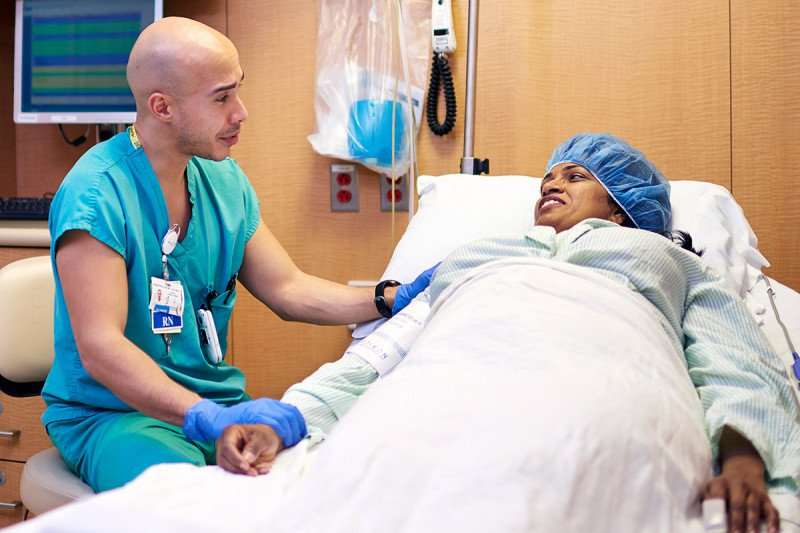 Clinical nurse III Henry Martinez with a patient