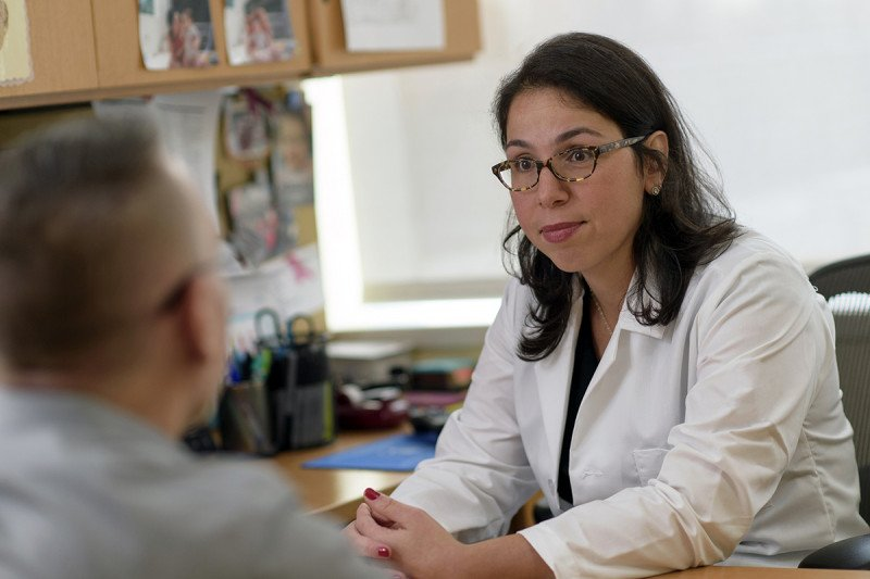 Medical oncologist and male breast cancer expert Ayca Gucalp speaks to male patient in her office.