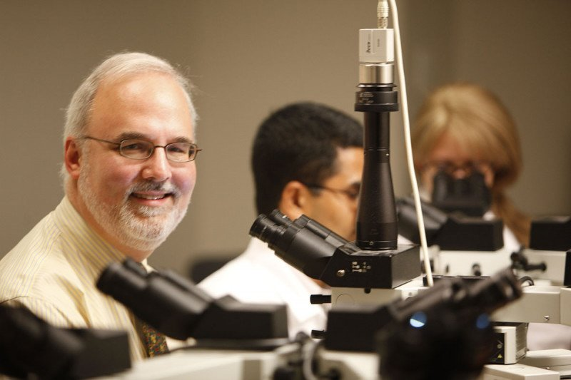 Pathologist David Klimstra sits in front of a microscope with colleagues.