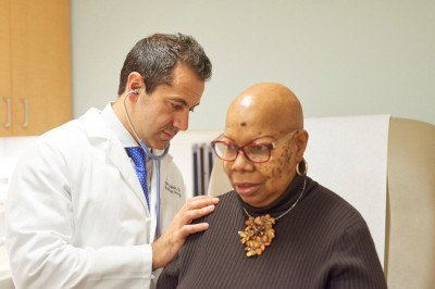 Oren Cahlon, MSK's Director of Proton Therapy, examines a patient.