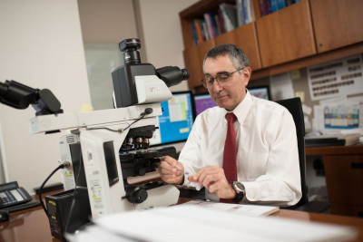 Ahmet Dogan, seated at a microscope, is one of the MSK pathologists who diagnoses lymphoma.